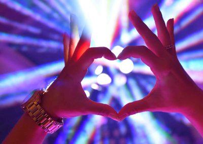 Zwei Hände bilden ein Herz vor Effektlicht Portfolio