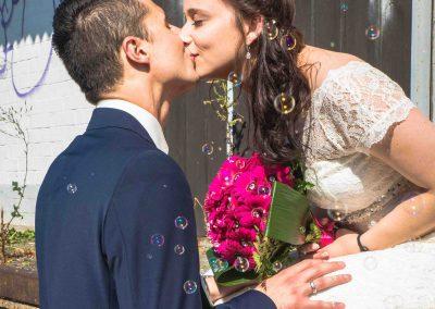 Ein festlich angezogener Mann küsst eine Frau im weissen Brautkleid