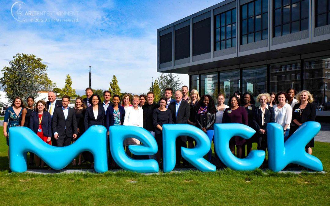 Arbeitnehmer der Firma Merck stehen hinter dem neuen Merck KGaA Firmenlogo