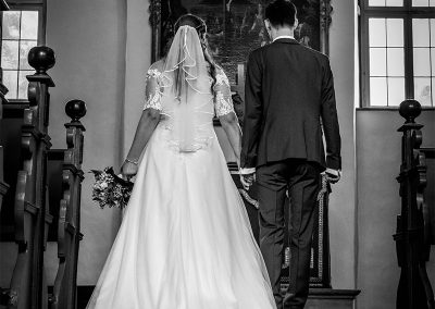 Brautpaar läuft den Mittelgang in der Kirche runter auf den Altar zu