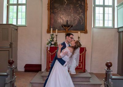Bräutigam küsst Braut romantisch vor dem Altar in der Kirche
