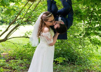 Bräutigam hängt vom Ast und beide küssen sich