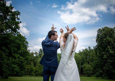 Brautpaar formt mit den Fingern das Wort Love in der Luft