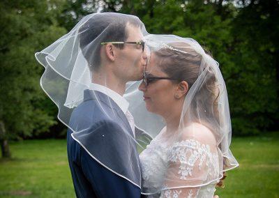 Bräutigam küsst Braut unter dem Schleier
