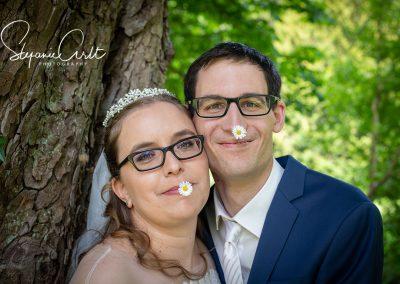 Brautpaar hat Gänseblümchen im Mund