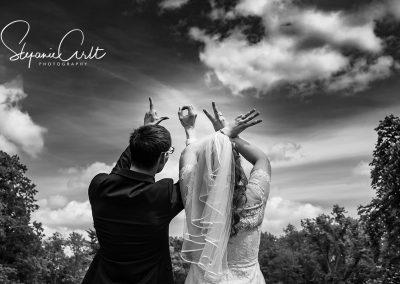 Brautpaar hält Hände in die höhe und formt das Wort Love