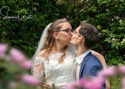 Brautpaar küsst sich romantisch auf Parkbank