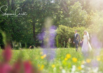 Brautpaar läuft über Wiese